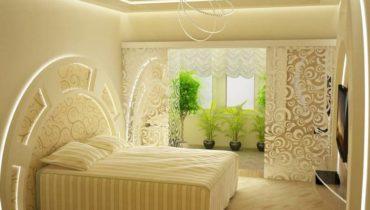 Светлый ванильный дизайн спальни украшен зелеными растениями