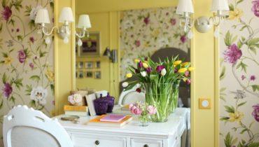 Цветочные обои с пастельно-желтыми вставками и белым письменным столиком.